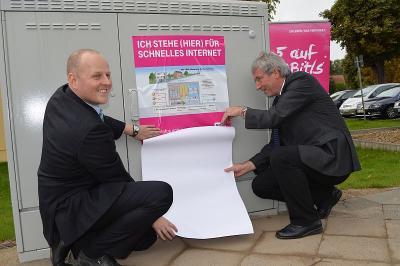Christian Stern und Bürgermeister Heiko Müller beim Plakate kleben. Mit diesen weist die Telekom auf ihren Netztausbau hin.