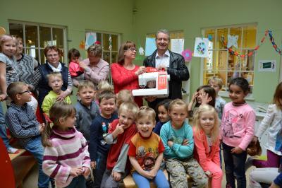 """Die neue Nähmaschine: Hans-Jürgen Döllefeld mit Veronika Menk. Kinder der Kita """"Märchenland"""" freuen sich mit. I Foto: Christiane Schomaker"""