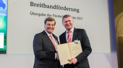 Enak Ferlemann (re.), parlamentarischer Staatssekretär und Mitglied des Bundestages, übergibt den Fördermittelbescheid an OSL-Landrat Siegurd Heinze (re.). Foto: BMVI