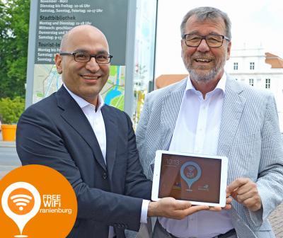 Alireza Assadi (Stadtwerke Oranienburg, li.) und Bürgermeister Hans-Joachim Laesicke gaben das neue Stadt-WLAN-Netz frei.
