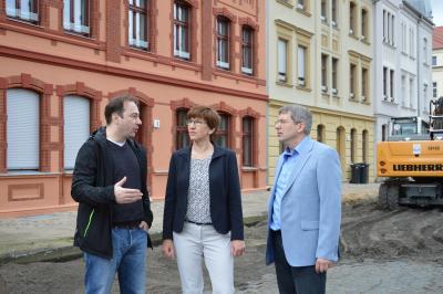 Die Ministerin vor den sanierten Wohnhäusern in der Bürgermeister-Jahn-Straße mit Bürgermeister Dr. Oliver Hermann und Marcel Elverich. I Foto: Christiane Schomaker