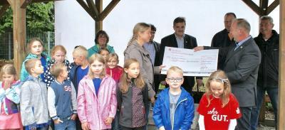 Udo Langer überreicht die Spende an die Initiatorin des Projektes Anja Wenzel. Im Vordergrund Schülerinnen und Schüler der Grundschule Schenklengsfeld.