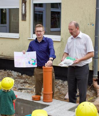 DRK-Präsident Oliver Wehner und Bürgermeister Thomas Mutze füllen beim feierlichen Spatenstich mit den Kindern der Einrichtung eine Zeitkapsel