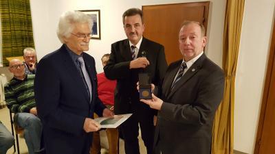 Bürgermeister Stefan Gensler (Bildmitte) und der Vorsitzende der Gemeindevertretung Udo Langer (rechts) überreichen Herrn Dieter Schenk (links) die Ehrenplakette der Gemeinde