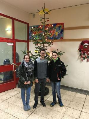 Leona Fabich (links) und Robin Breidenbach (rechts) mit Schülersprecher Daniel Vedder (Mitte) vor dem gestellten Weihnachtsbaum