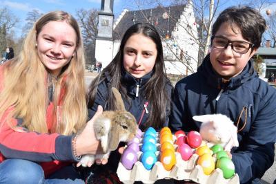Jungzüchterin Luisa-Sophie Wolf (links) präsentiert junge Osterhäschen zusammen mit Josephine und Danilo Janich; Foto: C. Henze