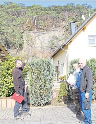 Geologe Dr. Manuel Lauterbach, David Kochannek von der Spezialfirma Schneider und Oberneisens Ortsbürgermeister Peter Pelk (von links) begutachten die Felssicherung an der Wand über der Herbachstraße. Foto: Maue-Klaeser