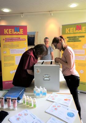 An der Schwarztlichtbox:  Gesundheits- und Krankenpflegerin Lydia Frei (links) und Hygienefachkraft Susen Bär (rechts),  Wirtschaftsleiterin Barbara Birtel (hinten) unterstützte bei der Aktion.