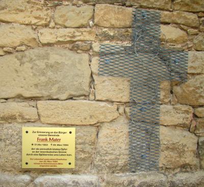 Diese Tafel an der Ostmauer der Mihlaer St. Martinskirche erinnert an den Tod des 20jährigen Frank Maters 1984 an der innerdeutschen Grenze unweit von Treffurt. Daneben ist ein Kreuz aus Streckmetall, dem Material des Grenzzaunes, angebracht..