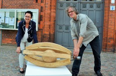 Insgesamt 40 kg bringt die Eichenholzarbeit auf die Waage. V. l. Annett Jura, Jost Löber   Foto: Stadt Perleberg