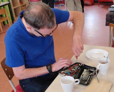 Freiwillige des Reparatur-Teams helfen defekte Geräte zu reparieren.