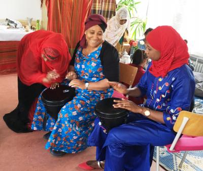 Auf dem Foto sind drei afrikanische Frauen beim Trommeln zu sehen. Foto: Christiane Betz/Stadtteilzentrum