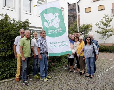 """Auch 2018 wird die """"Mayors for Peace"""" Flagge vor dem Rathaus zu sehen sein. Zur Premiere im letzten Jahr wurde diese mit mehreren Personen erstmalig gehisst (siehe Foto). Foto: Stadt Maintal"""