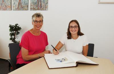 Foto zur Meldung: Holzwickedes Sportlerin des Jahres Denise Palberg trägt sich ins Goldene Buch der Gemeinde ein