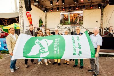 Stadtpräsident Norbert Thomas, Bürgermeister Frank Kracht und Alt-Bürgermeister Dieter Holtz zeigen, gemeinsam mit ihren ausländischen Gästen, Flagge. (Foto: Christian Thiele)