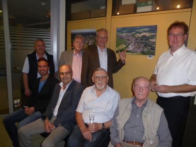 Foto zeigt Bürgermeister Weiher und Axel Häsler (rechts) mit Gästen im Erdgeschoss des Rathauses, wo jeder Stadtteil fotografisch vertreten ist – die Mehrzahl der Fotografien sind im Flurbereich des Ersten Stocks zu finden.