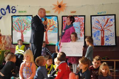 Bürgermeister Dr. Ronald Thiel übergibt Kitaleiterin Irina Franke den Scheck zum Kitageburtstag.  Foto: Beate Vogel/Stadt Pritzwalk