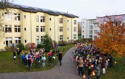 Von links: Blechbläser-Ensemble unter Leitung von Sven Biermann (Mitte) sowie die kleinen Sängerinnen und Sänger mit ihren Lehrkräften.