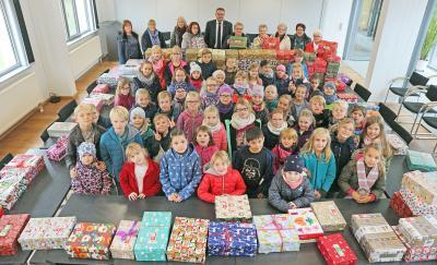 Lehrerinnen, Schülerinnen und Schüler der Grundschule Grasleben und die Weihnachtsdamen übergeben die liebevoll gepackten Schuhkartons an Samtgemeindebürgermeister Gero Janze. (Foto: Nico Jäkel)