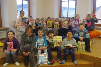 Die Kinder der 3. Klasse der Grundschule Röslau zeigen ihre gerade ausgeliehenen Bücher. Mit auf dem Bild Frau Gebhardt, die ehrenamtlich die Ortsbücherei verwaltet.