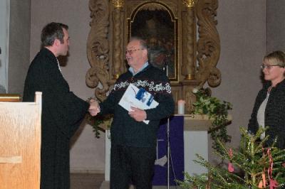 Pfr. Lindner und Frau Schweikhardt überreichen Hr. Gruber eine Urkunde des Kirchenmusikverbands und ein Geschenk der Kirchengemeinde. (Foto: K. Müller)