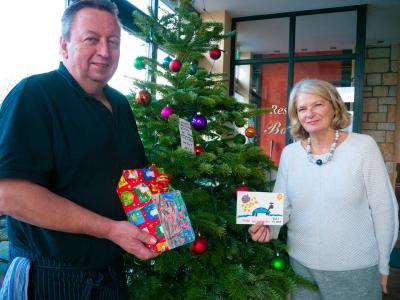 Kinderwünsche am Weihnachtsbaum: Bonne Vie-Betreiber Andreas Schauerte freut sich mit Gabriele Fischer-Krunke vom Kinderschutz-Zentrum über die ersten gespendeten Geschenke.