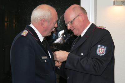 Dirk Lolies (rechts) zeichnet Seesters Wehrführer Hermann Stieler mit dem Deutschen Feuerwehr-Ehrenkreuz in Silber aus