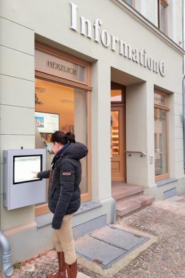 N. Drescher, Stadt Perleberg   Bürgerin probiert den Touch-Screen an der Stadtinformation, Großer Markt 12, aus.