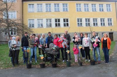 Junge Familien bei der Übergabe der Obstbäume