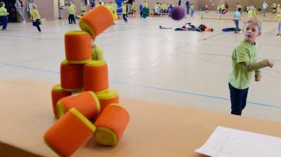 Volltreffer: In der Sporthalle konnten die 174 Jungen und Mädchen der Grundschule Merzen ihre sportliche Fitness testen - zum Beispiel beim Dosenwerfen. Foto: Christian Geers