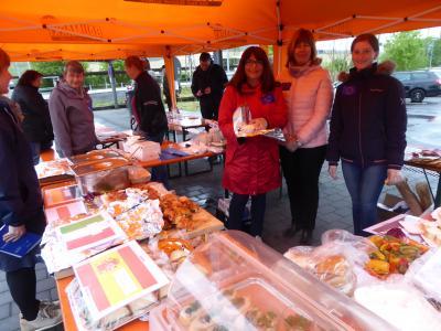 """Foto zeigt Gäste mit den Helferinnen und Helfern zur Aktion """"Europatag"""" am Wächtersbacher Bahnhof, inmitten den leckeren europäischen Speisen"""