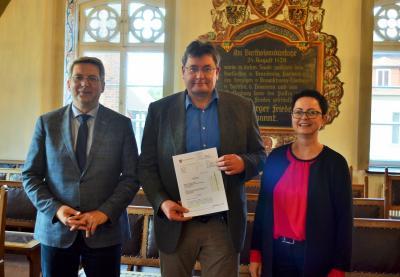 von Links: Bürgermeister Dr. Oliver Hermann, Perlebergs Museumsleiter Frank Riedel und Bürgermeisterin Annett Jura mit dem Zuwendungsbescheid I Foto: Nicole Drescher