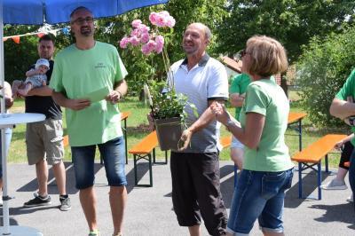 Der Vorsitzende Armin Hahn (links) überreicht zusammen mit seiner Frau Sabina einen Blumenstock an Hubert Schneider (Mitte), der seinen Garten unter dem Thema WEIN UND MEER präsentierte