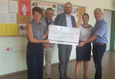 Kultusminister Piewarz (Bildmitte) übergibt den symbolischen Scheck