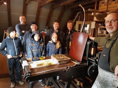 Peter Dettmann und Volker Scharnefsky mit Besuchern in der Ludwigsluster Litho-Werkstatt