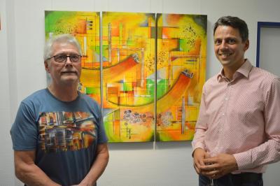 Frank Walkenhorst (l.) zusammen mit TGZ-Geschäftsführer Christian Fenske vor einem Bild des Wittenberger Elektromeisters I Foto: Martin Ferch