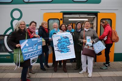 Mitglieder des Beirates für die Teilhabe von Menschen mit Behinderung und Gleichstellungs- und Integrationsbeauftragte Manuela Dörnenburg begrüßten fröhlich die Reisegruppe, insbesondere Carola und Thomas Szymanowicz aus Falkensee (blaue T-Shirts)
