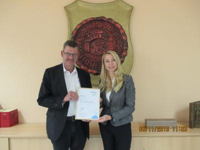 Frau Voß von der Firma Kyocera überreicht dem Bürgermeister die Urkunde