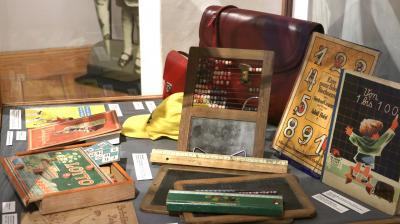 Stadt Perleberg | Schulutensilien wie Griffelkasten, Schiefertafel, Zeugnismappen und Fibeln werden in der Ausstellung präsentiert.