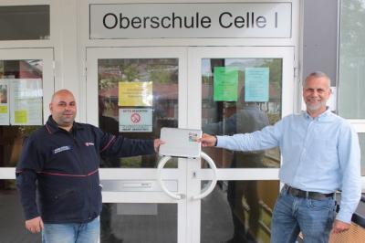 Der Schulleiter der Oberschule Celle I Sven Sievert (rechts) freut sich über die Chromebooks des Malteser Hilfsdienstes, welche von Mizgin Kizilyel (links) übergeben wurden.