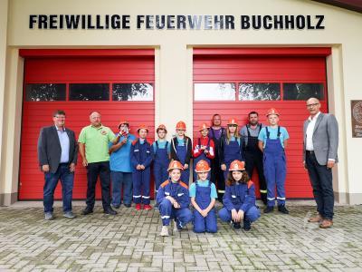 Der Buchholzer Feuerwehrnachwuchs trägt die neuen Helme, die Bürgermeister Dr. Ronald Thiel und Halldor Lugowski übergeben haben. Foto: Beate Vogel