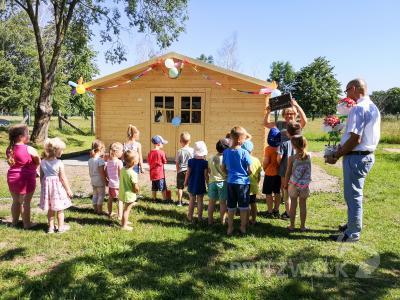 Kitaleiterin Birgit Schalm und die Kinder der Rappelkiste eröffnen gemeinsam mit Bürgermeister Dr. Ronald Thiel das neue Gartenhaus. Foto: Beate Vogel
