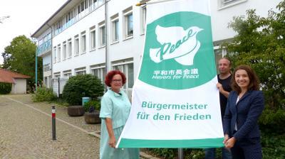 Bürgermeisterin Monika Böttcher hat gemeinsam mit Kommunalpolitiker*innen am Rathaus der Stadt Maintal die Flagge des Bündnisses Mayors for Peace / Bürgermeister für den Frieden gehisst. Foto: Stadt Maintal