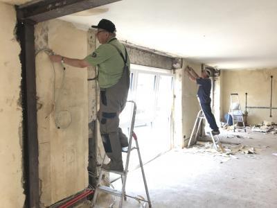 Ehrenamtliche befreien Wände und Decken von Tapeten
