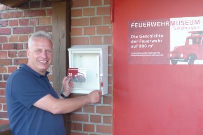 Der Vorsitzende Thomas Kolmes holt die Postkarte aus dem Briefkasten