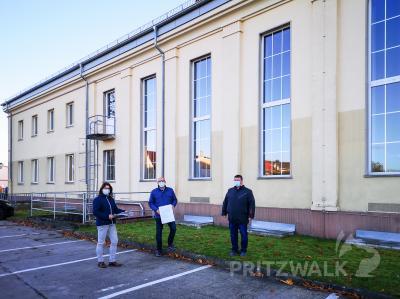 An der Nordfassade, vor der Andrea Asse, Bürgermeister Dr. Ronald Thiel und Halldor Lugowski den Zuwendungsbescheid präsentieren, wird später der Lift angebaut. Foto: Beate Vogel