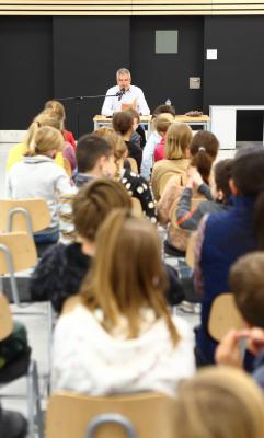 Bürgermeister Sven Siebert liest vor Fünftklässlern der Gebrüder-Grimm-Grundschule.