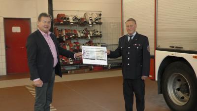 Bürgermeister Roland Pohlenz übergibt den Scheck in Höhe von 1180 € an Jugendfeuerwehrwart Gerd Paulo