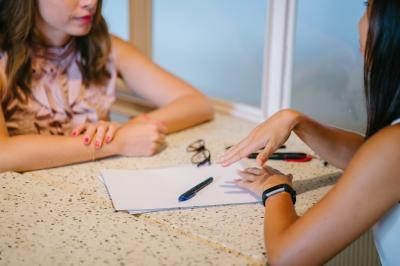 2 Frauen sitzen sich gegenüber und sprechen miteinander, zwischen ihnen liegen Papier und Stifte;  Foto von mentatdgt von Pexels