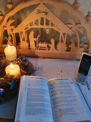 Vorschaubild mit Telefon, Gesangsbuch und Adventskranz